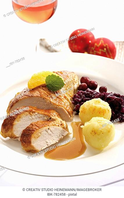 Roasted chicken breast on a plate with a salad containing orange segments in front of Christmas decorations