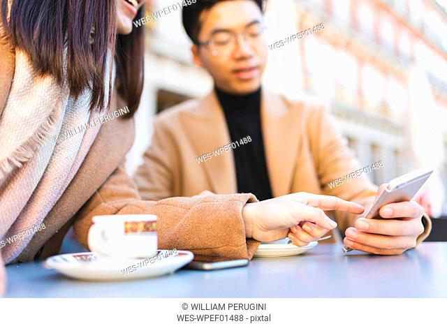 Spain, Madrid, young couple using cell phone in a cafe at Plaza Mayor