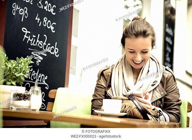 Smiling young woman sitting in street cafe using smartphone