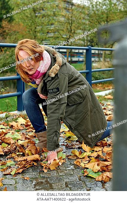 Woman slipping on wet autumn foliage