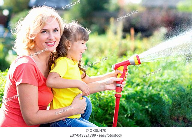 Pretty woman and her kid watering with hose in the garden
