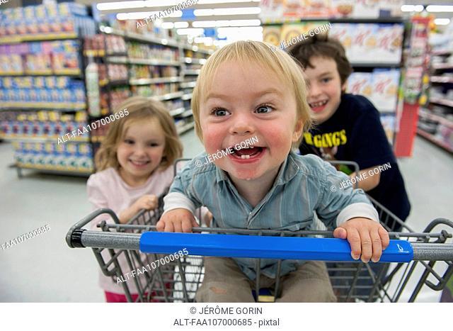 Children having fun in shopping cart