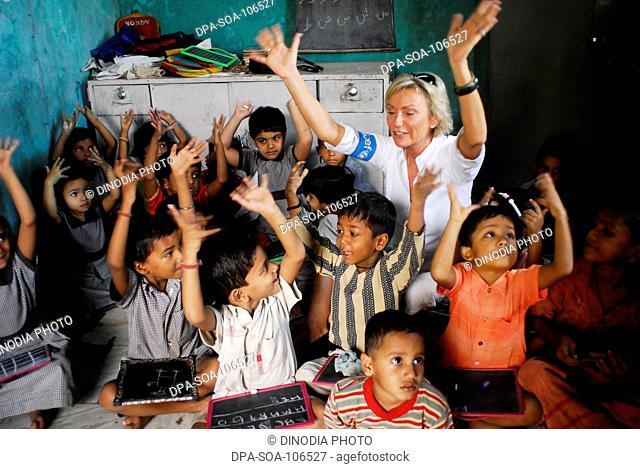 Sabine Christiansen in conversation with children at Amrae an NGO at Nehru Nagar ; Golibar Slum ;Santacruz ;Bombay Mumbai ; Maharashtra ; India NO MR