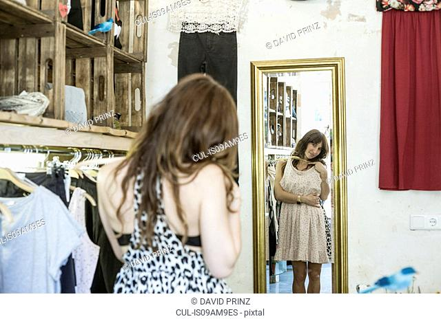 Mid adult woman holding dress in front of mirror in vintage boutique