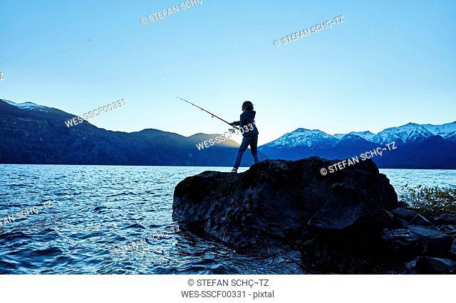 Argentina, Patagonia, Lago Futalaufquen, boy fishing in lake at dusk