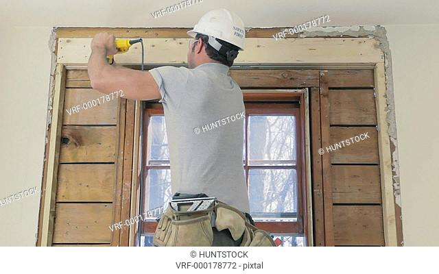 Carpenter using reciprocating saw to cut wall studs for wall removal around window