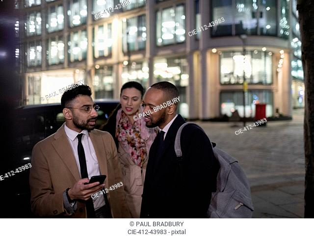 Business people with smart phone talking on city street at night