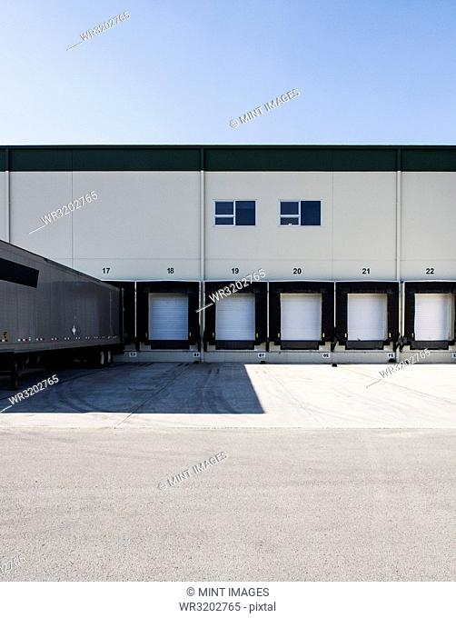 Exterior view of a warehouse loading dock with a truck trailer pulled up to one of the doors