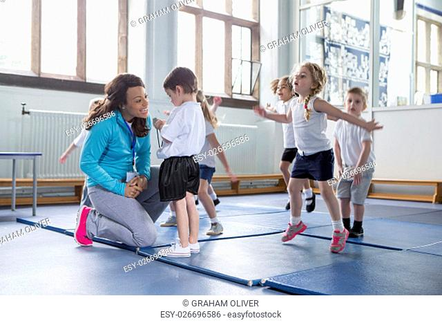 Nursery teacher reassuring one of her students during a physical education class