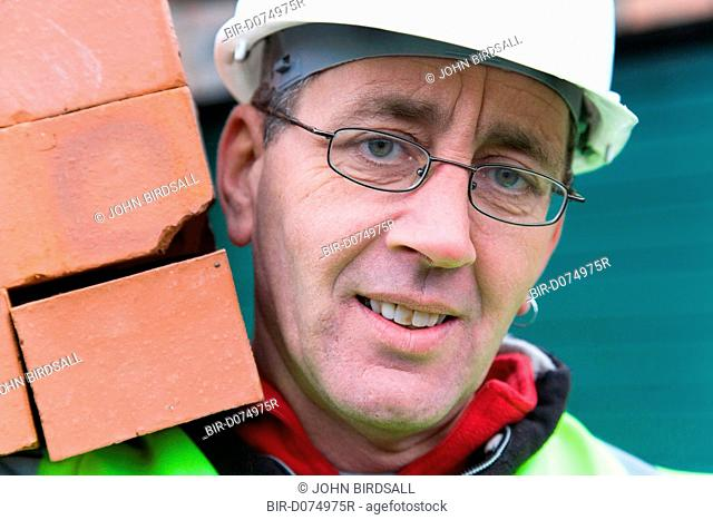 Builder carrying a hod of bricks