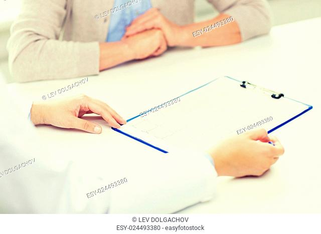 medicine, age, health care, cardiology and people concept - close up of senior woman and doctor hands with cardiogram meeting in medical office