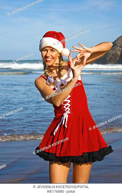 happy woman in christmas dress make a heart with fingers on the beach