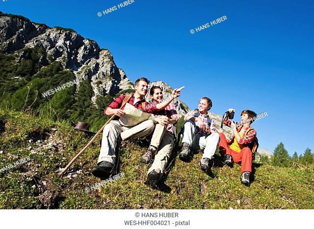 Austria, Salzburg County, Men and women sitting in alpine meadow