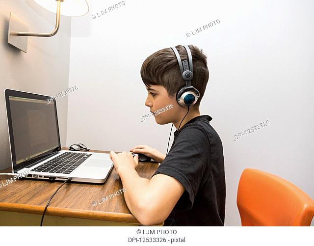 A young boy doing his homework on a small desk at his home and listening to headphones at the same time; Langley, British Columbia, Canada