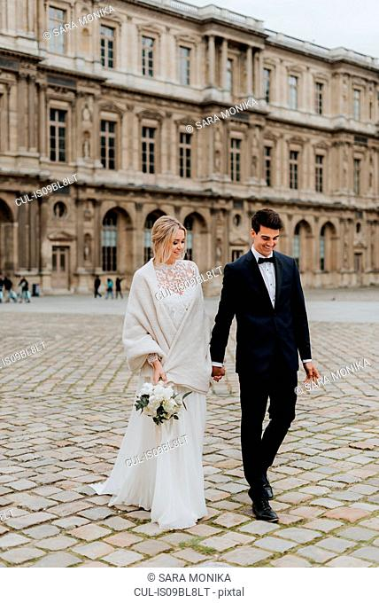 Bride and bridegroom on cobblestone street, Paris, France