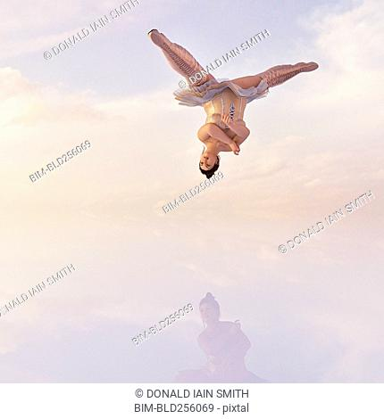 Woman wearing corset and boots upside-down in clouds