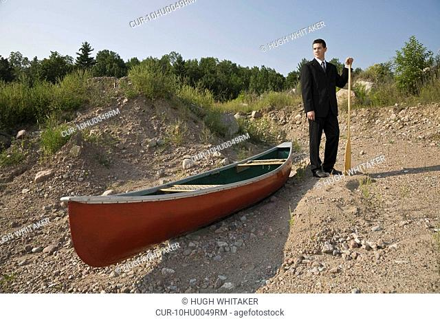 Man in dry river with canoe