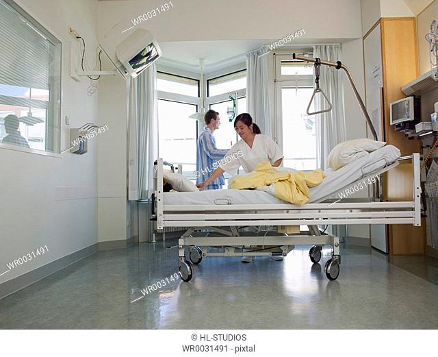 Female nurse changing bed sheet of patients bed