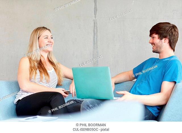 Young male and female students sitting on study space sofa using laptop at higher education college