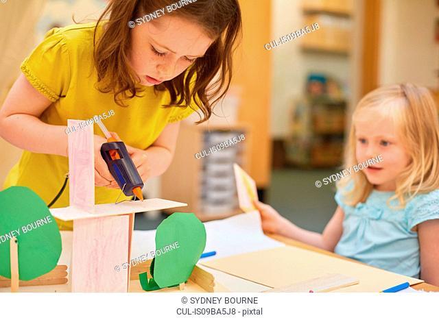 Primary schoolgirls making cardboard model at classroom desk
