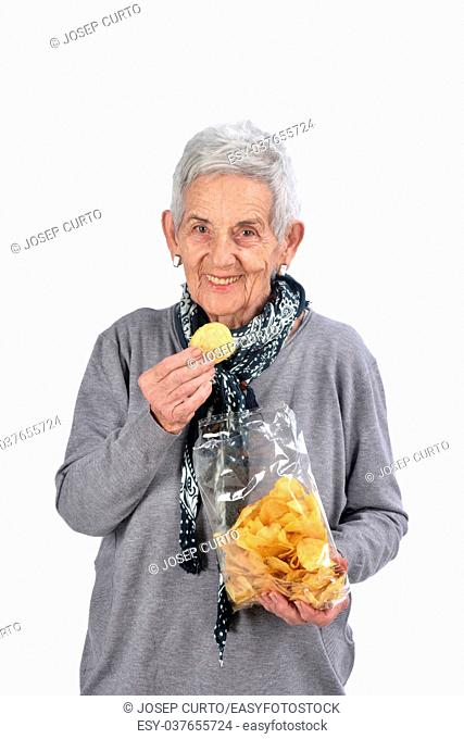 senior woman eating chips on white