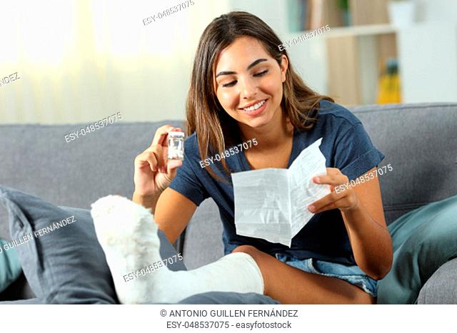Disabled happy woman reading pill leaflet sitting on a couch in the living room at home