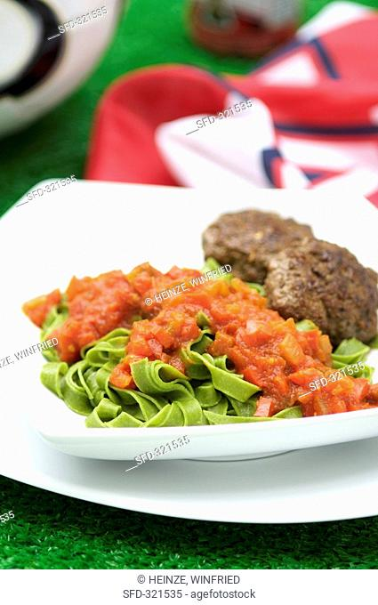 Green ribbon pasta with burgers and tomato sauce