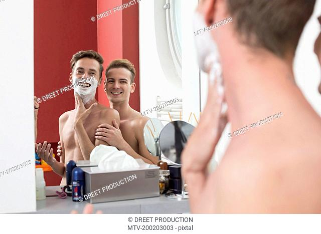 Homosexual couple caress each other while shaving, smiling