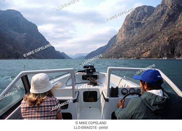 Couple in a Speedboat on a Lake Heading Towards Cliffs  Cabora Bassa Dam, Northern Mozambique