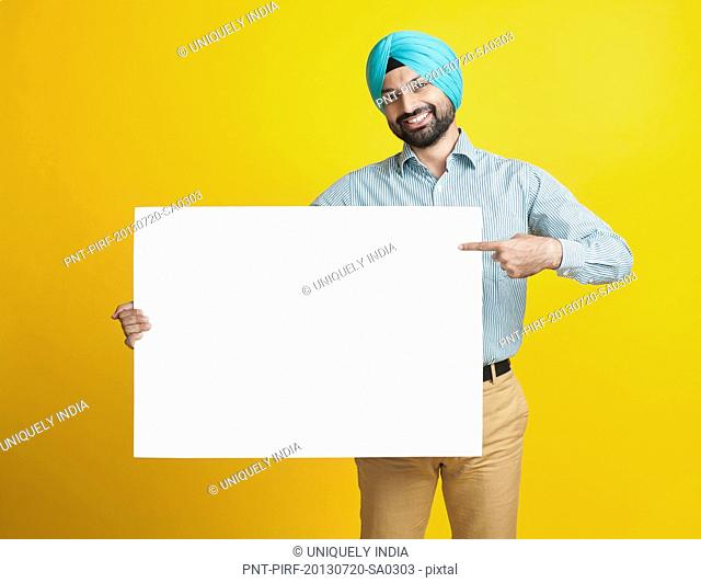 Portrait of a sikhman holding a blank placard and smiling