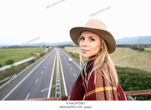 Portrait of young woman on motorway bridge