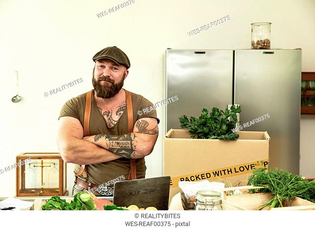 Owner of a delivery service for organic vegetables, standing proud in his kitchen