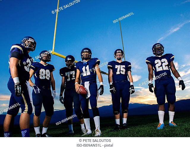 Portrait of teenage and young male american football team on pitch