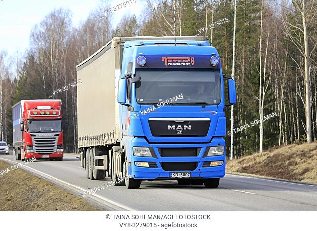 Tenhola, Finland - March 29, 2019: Two semi trailer trucks, Blue MAN and Red Scania haul goods along rural highway on a day of spring