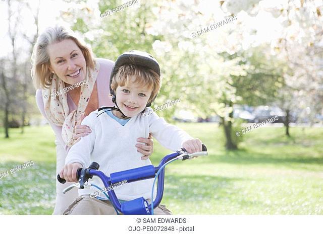 Smiling grandmother hugging grandson on bicycle in park