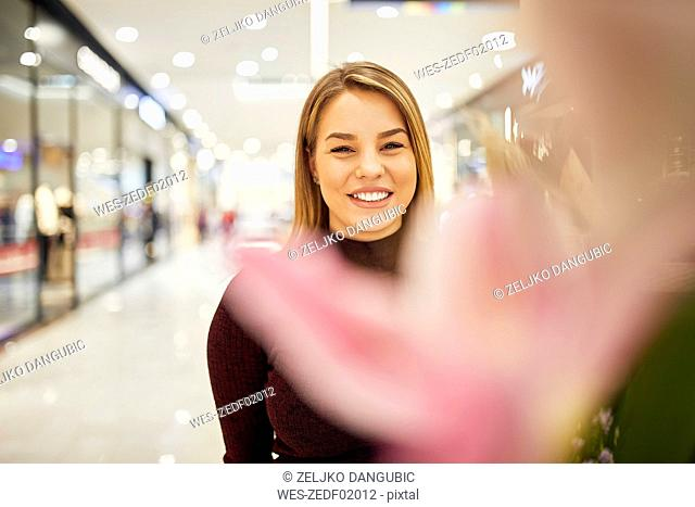 Portrait of smiling woman behind blossom in a shopping arcade