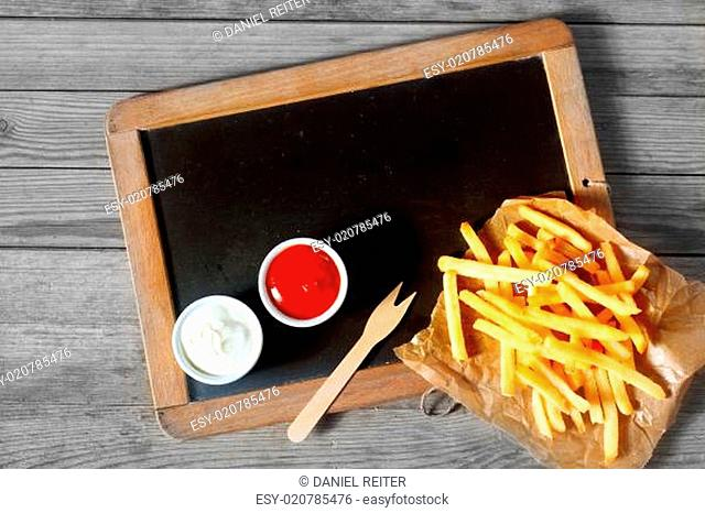 Fried Potatoes Fries and Sauces Above Chalkboard