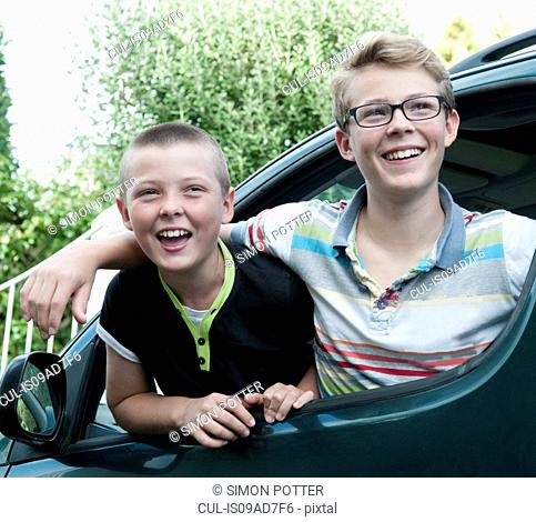 Portrait of two brothers leaning out of car window