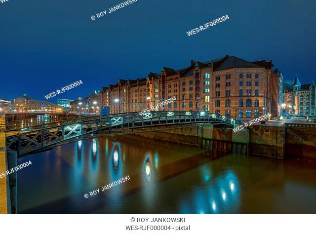 Germany, Hamburg, Jungfernbruecke crossing Zollkanal, old warehouse district (Speicherstadt) in the background by night