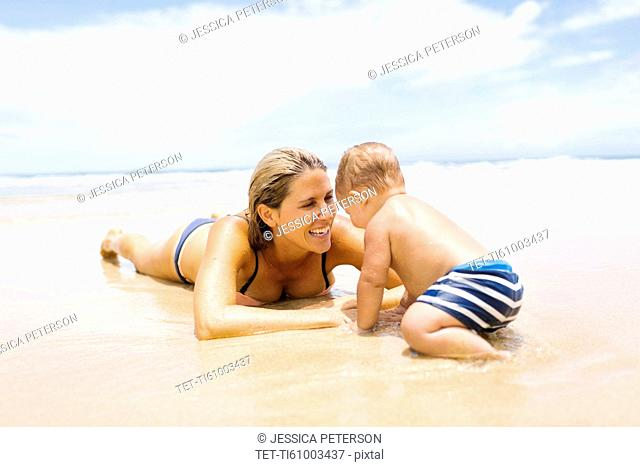 Mother playing with son (12-17 months) on beach