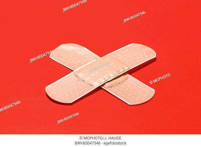 crossed band-aids against red background