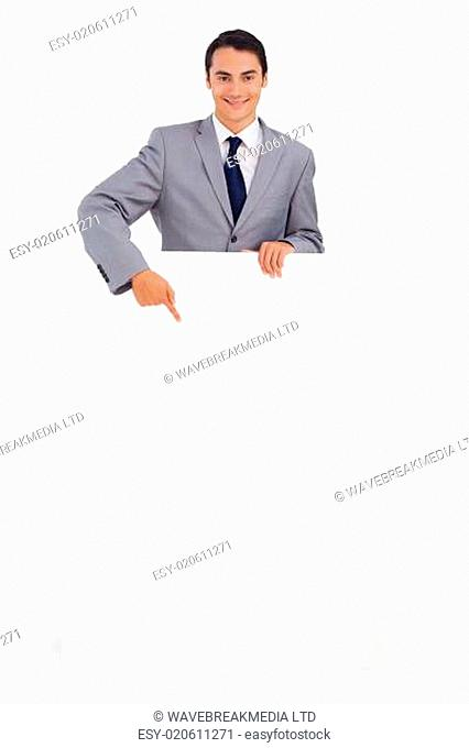 Good-looking man holding and pointing a big poster