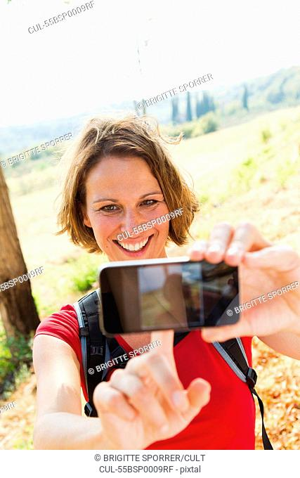 Woman photographing self in rural scene on camera phone