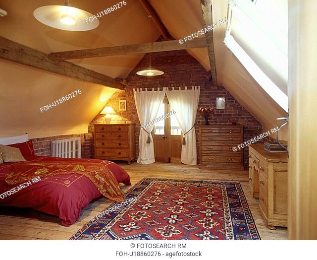 Blue+red oriental rug on wooden floor in large attic bedroom with white curtains and red duvet