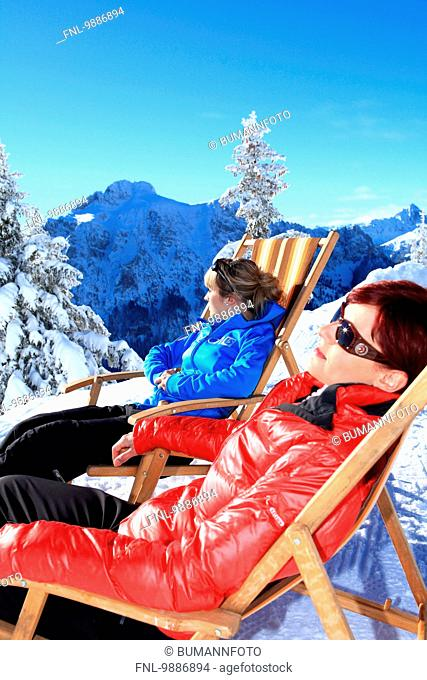 Two women in lounger in snow, Tegelberg, Ammergau Alps, Allgaeu, Bavaria, Germany, Europe