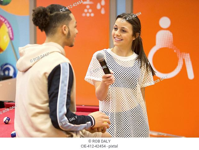 Teenage girl with microphone interviewing boy