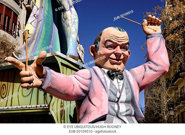 Papier Mache figure of a man in a pink jacket in the street during Las Fallas festival