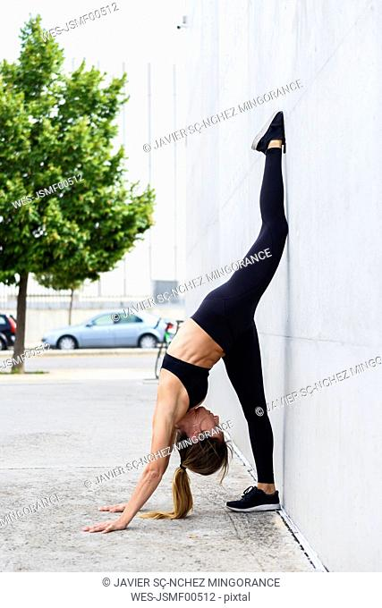 Athlete exercising standing splits on a white wall