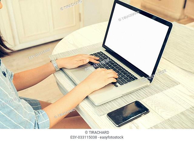 Female person sitting front open laptop computer and smart phone with blank empty screen for your information or content
