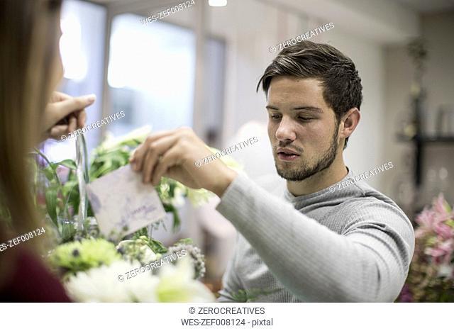 Man putting greeting card in flower arrangement